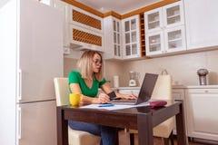 Επιχειρησιακή γυναίκα που εργάζεται στο σπίτι - προϋπολογισμός και πόροι χρηματοδότησης προγραμματισμού που πληρώνουν τους λογαρι στοκ φωτογραφία