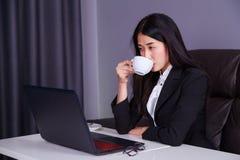 Επιχειρησιακή γυναίκα που εργάζεται στο φορητό προσωπικό υπολογιστή και που πίνει ένα φλυτζάνι Στοκ φωτογραφία με δικαίωμα ελεύθερης χρήσης