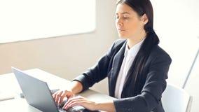 Επιχειρησιακή γυναίκα που εργάζεται στο lap-top στο γραφείο απόθεμα βίντεο