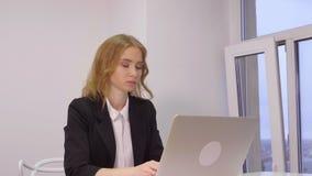 Επιχειρησιακή γυναίκα που εργάζεται στο PC σημειωματάριων κοντά στο παράθυρο στο επιχειρησιακό σύγχρονο γραφείο απόθεμα βίντεο