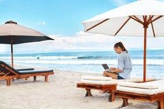 Επιχειρησιακή γυναίκα που εργάζεται on-line στην παραλία Ανεξάρτητος υπολογιστής Διαδίκτυο στοκ φωτογραφία με δικαίωμα ελεύθερης χρήσης