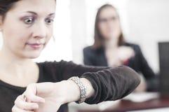 Επιχειρησιακή γυναίκα που ελέγχει το χρόνο Στοκ Φωτογραφίες