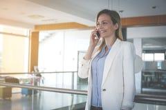 Επιχειρησιακή γυναίκα που διοργανώνει τη συζήτηση σχετικά με το έξυπνο τηλέφωνο Στοκ φωτογραφία με δικαίωμα ελεύθερης χρήσης