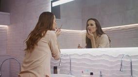 Επιχειρησιακή γυναίκα που κάνει makeup στο λουτρό Θηλυκό πρόσωπο ομορφιάς που εξετάζει τον καθρέφτη φιλμ μικρού μήκους