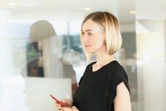 Επιχειρησιακή γυναίκα που κρατά ένα smartphone σε την Στοκ Φωτογραφίες
