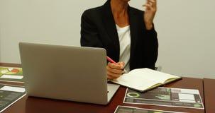 Επιχειρησιακή γυναίκα που μιλά στο κινητό τηλέφωνο γράφοντας σε ένα ημερολόγιο 4k φιλμ μικρού μήκους