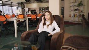 Επιχειρησιακή γυναίκα που μιλά στην τηλεφωνική συνεδρίαση σε μια πολυθρόνα απόθεμα βίντεο