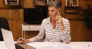 Επιχειρησιακή γυναίκα που παίρνει το κινητό τηλέφωνο χρησιμοποιώντας το lap-top 4k φιλμ μικρού μήκους