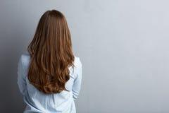 Επιχειρησιακή γυναίκα που στέκεται πίσω ενάντια στον γκρίζο τοίχο Στοκ Εικόνες