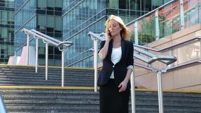 Επιχειρησιακή γυναίκα που στέκεται στα σκαλοπάτια και που μιλά σε ένα κινητό τηλέφωνο φιλμ μικρού μήκους