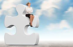 Επιχειρησιακή γυναίκα που στηρίζεται έναν γρίφο σε ένα υπόβαθρο ουρανού Στοκ Εικόνα