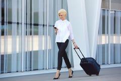 Επιχειρησιακή γυναίκα που ταξιδεύει με τη βαλίτσα και το κινητό τηλέφωνο Στοκ εικόνα με δικαίωμα ελεύθερης χρήσης