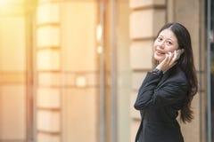 Επιχειρησιακή γυναίκα που φορά το έξυπνο ρολόι που χρησιμοποιεί το smartphone Στοκ εικόνα με δικαίωμα ελεύθερης χρήσης