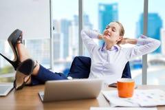επιχειρησιακή γυναίκα που χαλαρώνει ή που κοιμάται με τα πόδια της στο γραφείο μέσα στοκ φωτογραφία με δικαίωμα ελεύθερης χρήσης