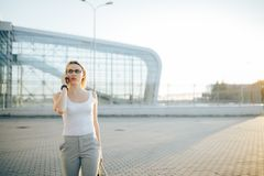 Επιχειρησιακή γυναίκα που χρησιμοποιεί ένα τηλέφωνο στεμένος σε υπαίθριο Στοκ Φωτογραφίες