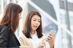 Επιχειρησιακή γυναίκα που χρησιμοποιεί ένα τηλέφωνο κυττάρων με το συνάδελφο και τη συζήτηση Στοκ εικόνες με δικαίωμα ελεύθερης χρήσης