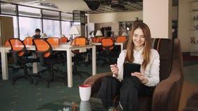 Επιχειρησιακή γυναίκα που χρησιμοποιεί την ταμπλέτα και το χαμόγελο οθόνης αφής στο γραφείο απόθεμα βίντεο