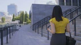 Επιχειρησιακή γυναίκα που χρησιμοποιεί το τηλέφωνο περπατώντας στο γραφείο απόθεμα βίντεο