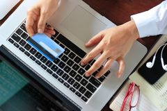 Επιχειρησιακή γυναίκα που χρησιμοποιεί το lap-top με την πιστωτική κάρτα υπό εξέταση στοκ φωτογραφία