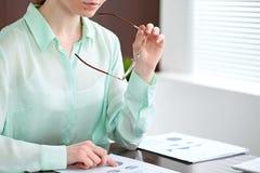 Επιχειρησιακή γυναίκα που ψάχνει τα οικονομικά έγγραφα στο γραφείο στοκ εικόνα με δικαίωμα ελεύθερης χρήσης