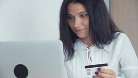 Επιχειρησιακή γυναίκα που ψωνίζει on-line με την πιστωτική κάρτα και το lap-top στο γραφείο απόθεμα βίντεο