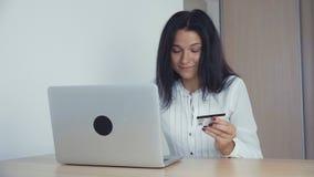 Επιχειρησιακή γυναίκα που ψωνίζει on-line με την πιστωτική κάρτα και το lap-top στο γραφείο φιλμ μικρού μήκους