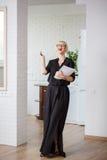 Επιχειρησιακή γυναίκα σε ένα μαύρο φόρεμα με ένα περιοδικό για τα πρακτικά Στοκ φωτογραφία με δικαίωμα ελεύθερης χρήσης