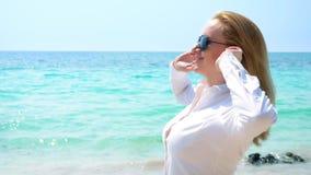 Επιχειρησιακή γυναίκα στα γυαλιά ηλίου στην παραλία Χαίρεται για τη θάλασσα και τον ήλιο Ξεκούμπωσε το πουκάμισό της και αναπνέει στοκ φωτογραφία