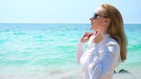 Επιχειρησιακή γυναίκα στα γυαλιά ηλίου στην παραλία Χαίρεται για τη θάλασσα και τον ήλιο Ξεκούμπωσε το πουκάμισό της και αναπνέει στοκ εικόνα