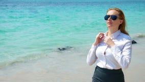 Επιχειρησιακή γυναίκα στα γυαλιά ηλίου στην παραλία Χαίρεται για τη θάλασσα και τον ήλιο Ξεκούμπωσε το πουκάμισό της και αναπνέει στοκ φωτογραφίες