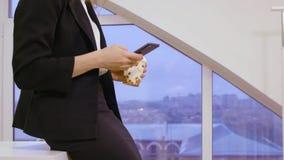 Επιχειρησιακή γυναίκα στα υψηλά τακούνια και το επιχειρησιακό κοστούμι που χρησιμοποιούν το κινητό τηλέφωνο στην αρχή απόθεμα βίντεο