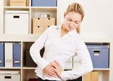 Επιχειρησιακή γυναίκα στην αρχή με τον πόνο στην πλάτη Στοκ Φωτογραφία