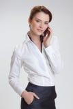 Επιχειρησιακή γυναίκα στην αρχή με το telephon Στοκ Εικόνες