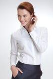 Επιχειρησιακή γυναίκα στην αρχή με το telephon Στοκ Φωτογραφία