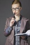 Επιχειρησιακή γυναίκα στην επιχειρησιακή γυναίκα γυαλιών σε ένα κοστούμι σκεπτικά Στοκ Φωτογραφίες