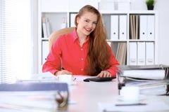 Επιχειρησιακή γυναίκα στην κόκκινη μπλούζα που κάνει την έκθεση, που υπολογίζει ή που ελέγχει την ισορροπία Στοκ εικόνα με δικαίωμα ελεύθερης χρήσης