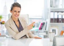 Επιχειρησιακή γυναίκα στο γραφείο που δείχνει στο διάστημα αντιγράφων Στοκ εικόνα με δικαίωμα ελεύθερης χρήσης