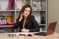 Επιχειρησιακή γυναίκα στο γραφείο που μιλά στο τηλέφωνο που εξετάζει το όργανο ελέγχου Στοκ Εικόνες