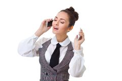 Επιχειρησιακή γυναίκα στο γραφείο της σε δύο τηλέφωνα Στοκ Φωτογραφία