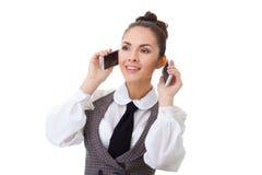 Επιχειρησιακή γυναίκα στο γραφείο της σε δύο τηλέφωνα Στοκ Εικόνα