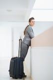 Επιχειρησιακή γυναίκα στο επιχειρησιακό ταξίδι με την τσάντα ροδών Στοκ Φωτογραφία