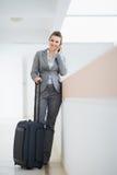 Επιχειρησιακή γυναίκα στο επιχειρησιακό ταξίδι με την τσάντα ροδών Στοκ Φωτογραφίες