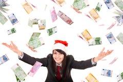 Επιχειρησιακή γυναίκα στο καπέλο santa με τα πετώντας χρήματα. Στοκ Φωτογραφίες