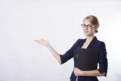 Επιχειρησιακή γυναίκα στο σκοτεινό σακάκι που παρουσιάζει κάτι Στοκ Φωτογραφία
