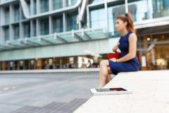 Επιχειρησιακή γυναίκα στο υπόβαθρο με ένα έξυπνο τηλέφωνο Στοκ Φωτογραφίες