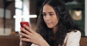 Επιχειρησιακή γυναίκα χρησιμοποιώντας app στο smartphone στον καφέ και texting στο κινητό τηλέφωνο Όμορφος περιστασιακός θηλυκός  απόθεμα βίντεο