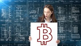 Επιχειρησιακή γυναίκα Bauty που στέκεται στο κοστούμι με το λογότυπο Bitcoin για να επεξηγήσει τη χρήση του bitcoin για τις εμπορ Στοκ Εικόνα