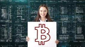 Επιχειρησιακή γυναίκα Bauty που στέκεται στο κοστούμι με το λογότυπο Bitcoin για να επεξηγήσει τη χρήση του bitcoin για τις εμπορ Στοκ Εικόνες