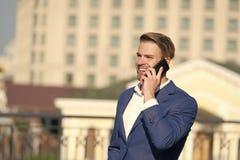 Επιχειρησιακή επικοινωνία και νέα τεχνολογία Ευτυχής επιχειρηματίας με το smartphone στο ηλιόλουστο πεζούλι Χαμόγελο ατόμων στο ε στοκ εικόνες