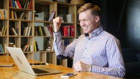 Επιχειρησιακή επιτυχία - ευτυχής δημιουργικός νεαρός άνδρας με το lap-top απόθεμα βίντεο